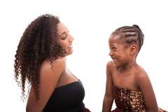 Μητέρα αφροαμερικάνων με την κόρη της που εξετάζει και που χαμογελά Στοκ φωτογραφίες με δικαίωμα ελεύθερης χρήσης