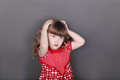 红色礼服的美丽的小女孩接触她的头 免版税库存图片