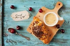 鲜美早餐用新新月形面包、咖啡、樱桃和笔记关于一张木桌 免版税库存图片