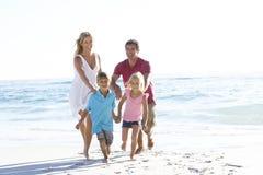 Νέα οικογένεια που τρέχει κατά μήκος της αμμώδους παραλίας στις διακοπές Στοκ Εικόνες