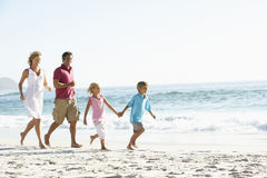 Νέα οικογένεια που τρέχει κατά μήκος της αμμώδους παραλίας στις διακοπές Στοκ εικόνες με δικαίωμα ελεύθερης χρήσης