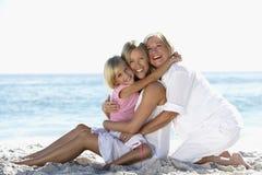 有放松在海滩的孙女和女儿的祖母 库存照片