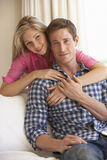 一起放松在沙发的年轻夫妇在家 免版税库存照片