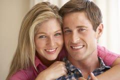 一起放松在沙发的年轻夫妇在家 免版税图库摄影