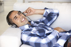 Χαλάρωση νεαρών άνδρων που ακούει τη μουσική στο σπίτι Στοκ Εικόνες