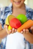 Νέο κορίτσι που κρατά τα πλαστικά φρούτα και λαχανικά Στοκ Φωτογραφία