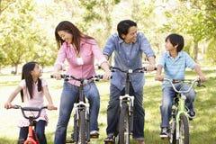 亚洲家庭骑马自行车在公园 库存图片