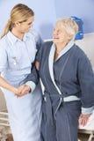 护理帮助的资深妇女在床外面在医院 免版税库存照片