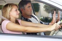 教十几岁的女儿的紧张的父亲驾驶 免版税库存图片