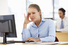 工作在书桌的被注重的女实业家在繁忙的办公室 免版税库存照片