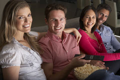 Группа в составе друзья сидя на софе смотря ТВ совместно Стоковые Изображения