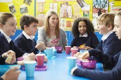 有老师的学童坐在表上吃午餐的 免版税库存图片