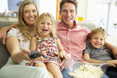 Οικογενειακή χαλάρωση στην τηλεόραση προσοχής καναπέδων από κοινού Στοκ εικόνες με δικαίωμα ελεύθερης χρήσης