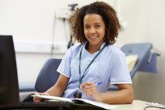 运作在书桌的女性护士画象在办公室 免版税库存照片