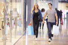 愉快的在商城的夫妇运载的袋子 免版税库存照片