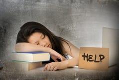 年轻人相当亚裔中国女学生睡着在她膝上型计算机学习劳累了过度与在她的书桌上的帮助标志 库存照片