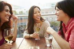 享受饮料的三个女性朋友在室外屋顶酒吧 库存照片