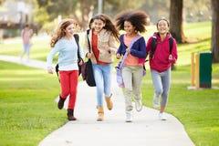 跑往照相机的小组女孩在公园 免版税库存照片