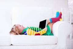 有片剂计算机的小女孩在一个白色长沙发 库存图片