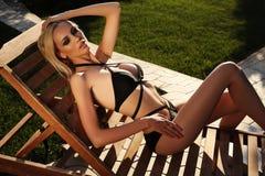 放松在游泳池旁边的比基尼泳装的性感的白肤金发的妇女 库存图片