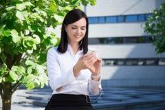 与智能手机的年轻女商人听的音乐在城市同水准 免版税库存照片