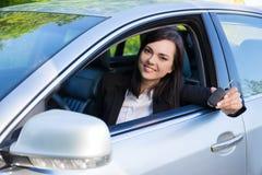 司机显示新的汽车钥匙和汽车的女商人 免版税图库摄影