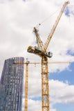 Δύο μεγάλοι γερανοί κατασκευής με τον ουρανοξύστη και το νεφελώδη ουρανό Στοκ Φωτογραφία