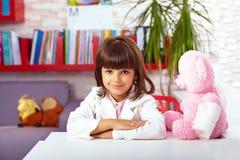 假装美丽的小女孩她是一位医生在医院 免版税图库摄影