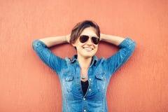 Ультрамодная девушка брюнет, делающ выражения стороны, усмехающся и смеющся над против оранжевой изолированной предпосылки, уклад Стоковое Изображение