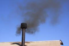 Στέγη μετάλλων με την καπνοδόχο που ρεύεται το μαύρο καπνό Στοκ εικόνα με δικαίωμα ελεύθερης χρήσης