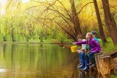 一起钓鱼在美丽的池塘附近的愉快的孩子 免版税库存图片