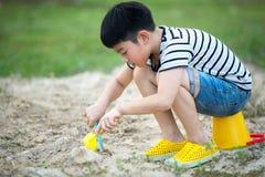 使用与玩具的亚裔男孩在庭院里 免版税图库摄影