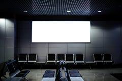 Общественная коммерчески доска в ждать залы авиапорта с пустыми стульями Стоковая Фотография RF