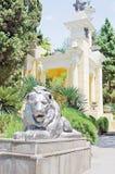 一头狮子的雕塑在摩尔人注视旁边的在索契树木园 免版税库存图片