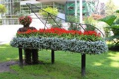 与花的钢琴在公园 免版税库存照片