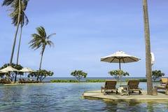 与热带手段的完善的海滩游泳池放松 图库摄影