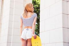 有滑板的性感的女性少年 免版税图库摄影