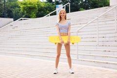 站立与滑板的女性少年 免版税库存照片