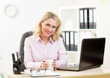中部变老了工作在膝上型计算机和饮用的咖啡的女实业家 免版税库存照片
