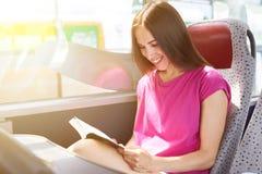 妇女阅读书在公共汽车上 免版税图库摄影
