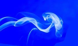 在蓝色背景的抽象白色烟漩涡 免版税库存图片