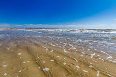 洗涤在加尔维斯顿海滩沙子的海浪  免版税库存图片