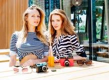 坐在夏天咖啡馆的两个时尚美丽的女孩 在桌上是美丽的葡萄酒照相机和橙色饮料从a的秸杆 免版税库存图片
