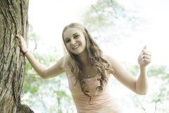 站立在绿色夏天的美丽的微笑的女孩 免版税库存图片
