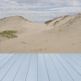 Пустая деревянная, голубая таблица готовая для вашего монтажа дисплея продукта с дюнами песка в предпосылке, Великобритании Стоковая Фотография RF