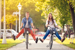 在自行车的愉快的滑稽的夫妇骑马 库存照片