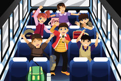 唱歌和跳舞在校车里面的小学生 免版税库存照片