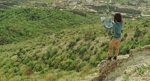 有室外的地图的远足者妇女 库存图片