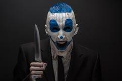 Ужасный клоун и тема хеллоуина: Шальной голубой клоун в черном костюме с ножом в его руке изолированной на темной предпосылке в Стоковое Изображение RF