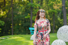花花圈和一件明亮的礼服的美丽的少妇坐草画象本质上,生活,微笑喜悦  免版税库存图片